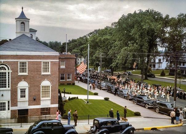 Парад День Памяти Павших в Войнах движется по главной улице Сауттингтон, Коннектикут, май 1942 года.Небольшое количество зрителей объясняется тем, что военные заводы города работали в этот