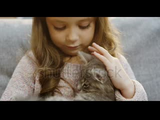 Stock-footage-close-up-of-the-cute-small-girl-with-long-blonde-hair-sitting-on-t