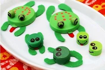 Лягушки из крышек Простые поделки лягушек можно сделать из обычных пластиковых крышечек от бутылок.Рожицы лягушкам и точки на спинке рисуем перманентным маркером. Лапки и язык делаем из картона.