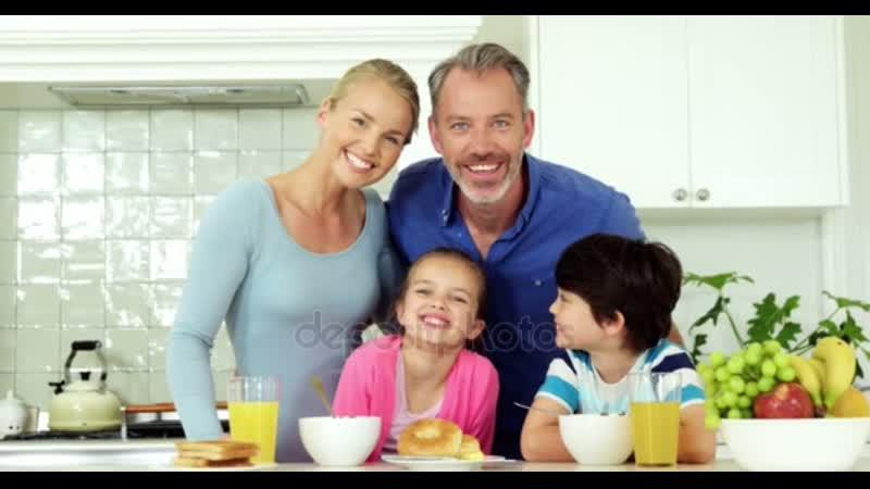 Портрет улыбающейся семьи стоящей на кухне