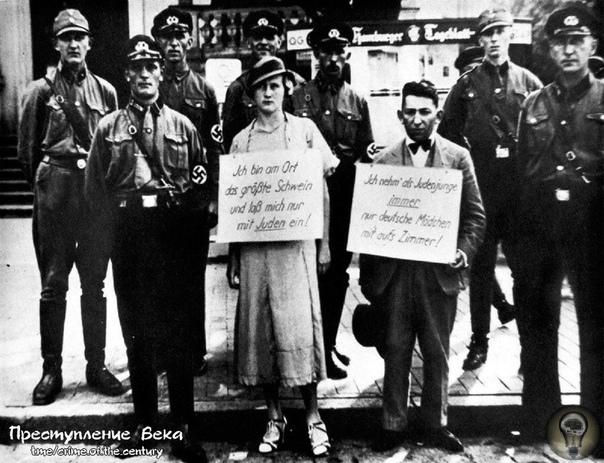 Штурмовики позируют вместе с нарушителями закона о расовой чистоте. На шее женщины плакат «Я большая свинья и я даю только евреям!».На шее мужчины плакат «Я еврей, только что пригласивший