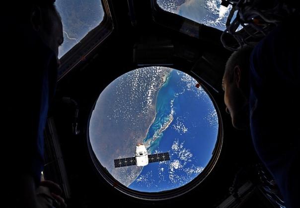 Астронавты Ник Хейг и Дэвид Сен-Жак наблюдают, как космический корабль Dragon с грузом прибывает на Международную космическую станцию