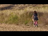 stock-footage-young-woman-wearing-a-dress-riding-vintage-bicycle-in-the-field-during-sunset-on-hot-summer-day.--.mp4