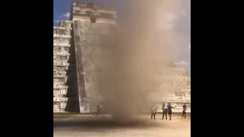 Пыльный вихрь рядом с пирамидой Кукулькана построенной цивилизации майя Мексика Чичен Ица 22 марта 2019