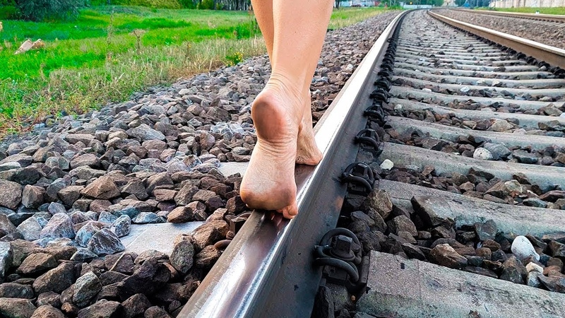 Bare feet walk on the rails showing my soles