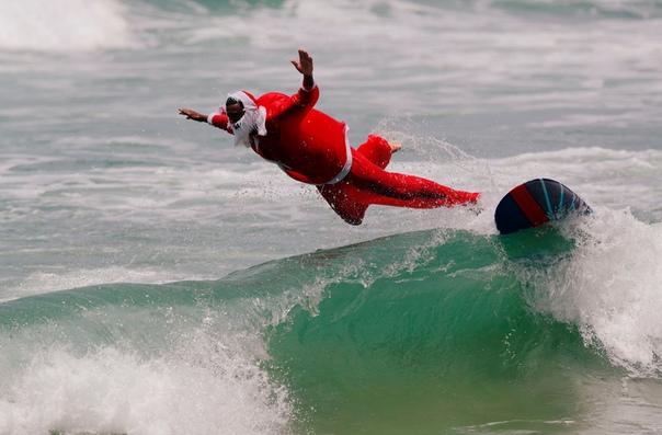 Инструктор по серфингу Карлос Баия занимается серфингом в костюме Санта-Клауса на пляже Маресиас в Сан-Себастьян, Бразилия