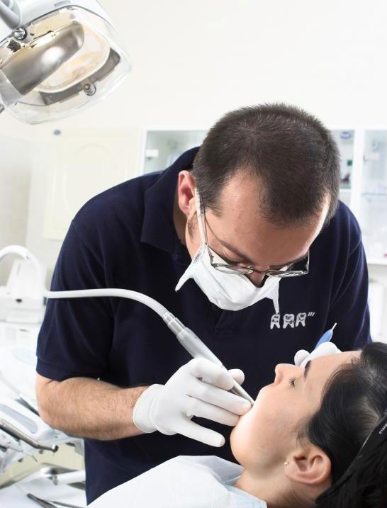 Человек, устанавливающий себе зубную пломбу с помощью стоматолога.