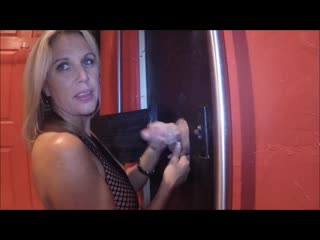 Sultry mature blonde in fishnets jerks off a glory hole cock video