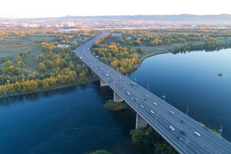Октябрьский мост. Белое здание с синей полосой под крышей — насосная станция СГК
