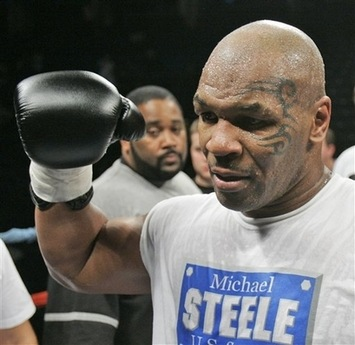 Mike Tyson raises his glove after fighting Corey 'T-Rex' Sanders in an...
