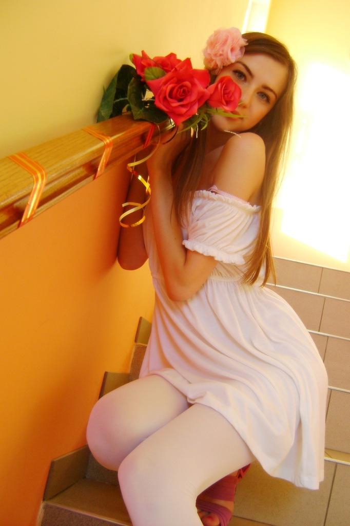 В белом платье и белых леггинсах с букетом роз