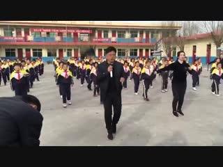 Директор китайской школы танцует с детьми на переменах