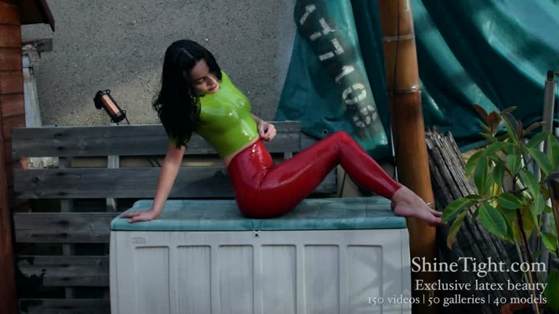Beautiful ShineTight model in green latex top, red latex leggings thigh-high leather boots