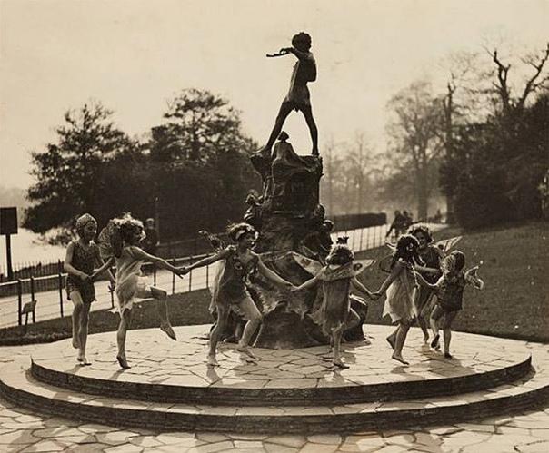 Дети танцуют вокруг статуи Питера Пэна в Кенсингтонском саду