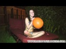 Cute teen blows up balloons till they pop in her face outside in bikini