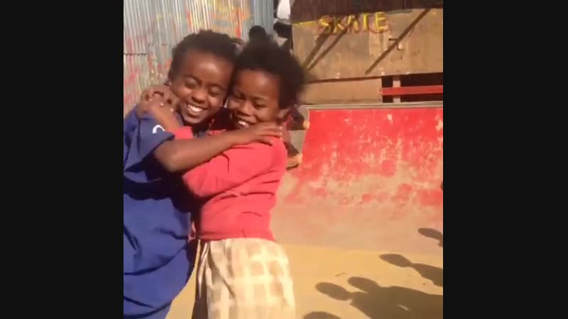 Two girls in close embrace as they skate together. Addis Ababa, Ethiopia.