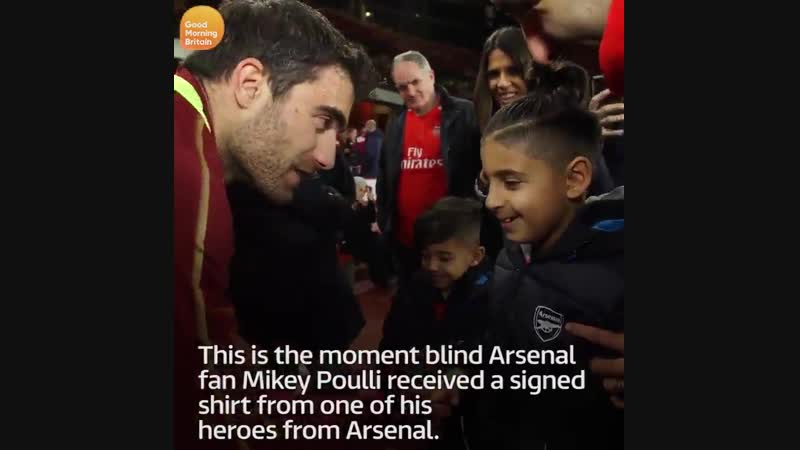 Blind Arsenal fan Mikey Poulli receives a signed shirt from Sokratis his football hero