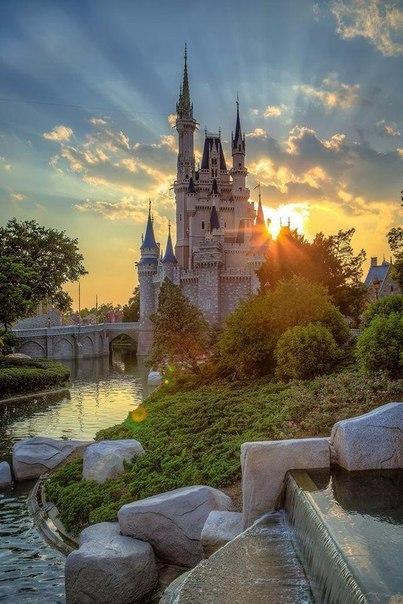 Замок Золушки на фоне заходящего солнца. Диснейленд, США.