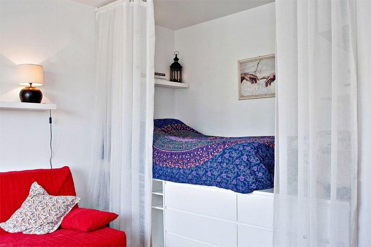 Интерьер студии 26 м: зона спальни – в нише за легкими занавесками, в высоком основании кровати устроены системы хранения.