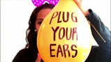 Woman blows to pop a balloon hold your ears