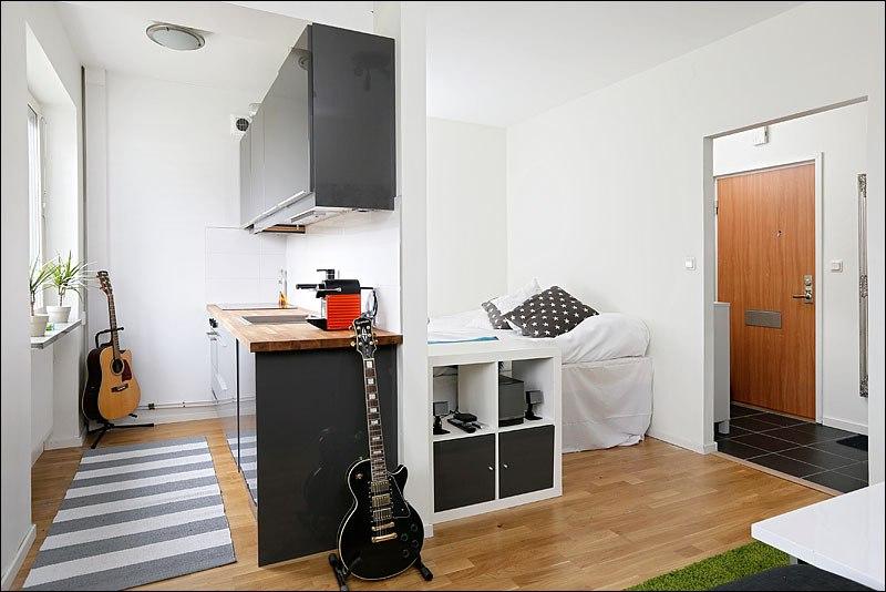 Квартира-студия почти 27 м: одна половина квадратной комнаты разделена перегородкой на кухню и спальню, а во второй организована гостиная.