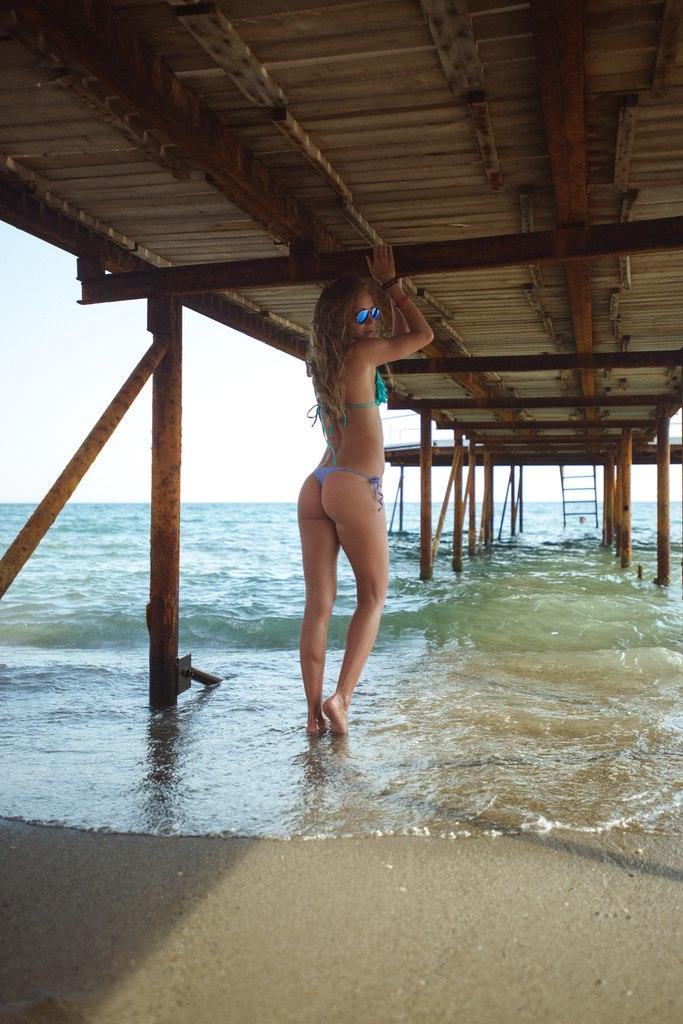 Тёлок раздевают на пляже 8 фотография