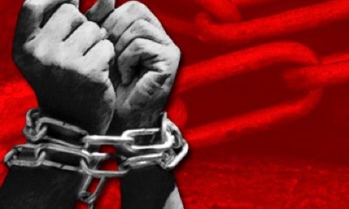 Руки в кайданай, на фоні червоний прапор