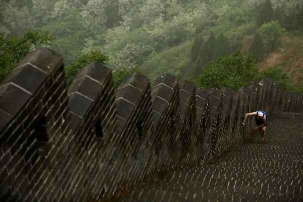 Уставший бегун на крутом участке Huangyaguan Великой стены в Great Wall Marathon (Пекин, Китай)