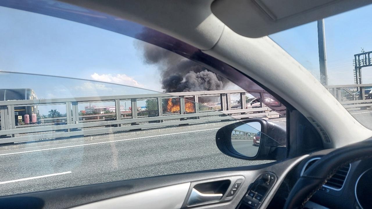 На 55 километре внешней стороны КАД, после съезда на Октябрьскую набережную, на обочине горит Mazda ...