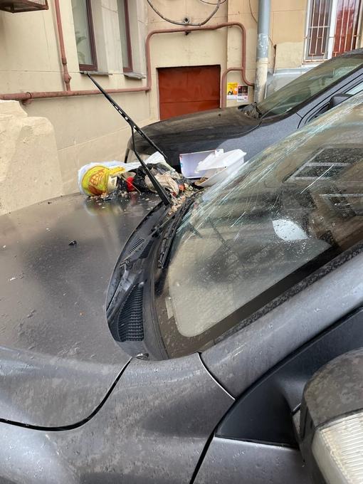 Кто то выбросил мусор из окна на лобовое припаркованной под окнами машины Ивановская 19