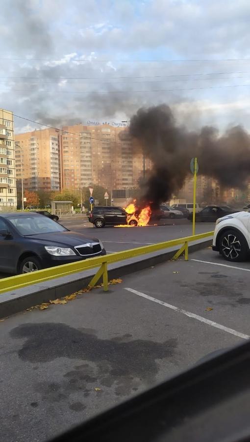 По адресу Поселок Тельмана 2Б горит машина на парковке ТЦ В машине никого нет. У соседней машины на...