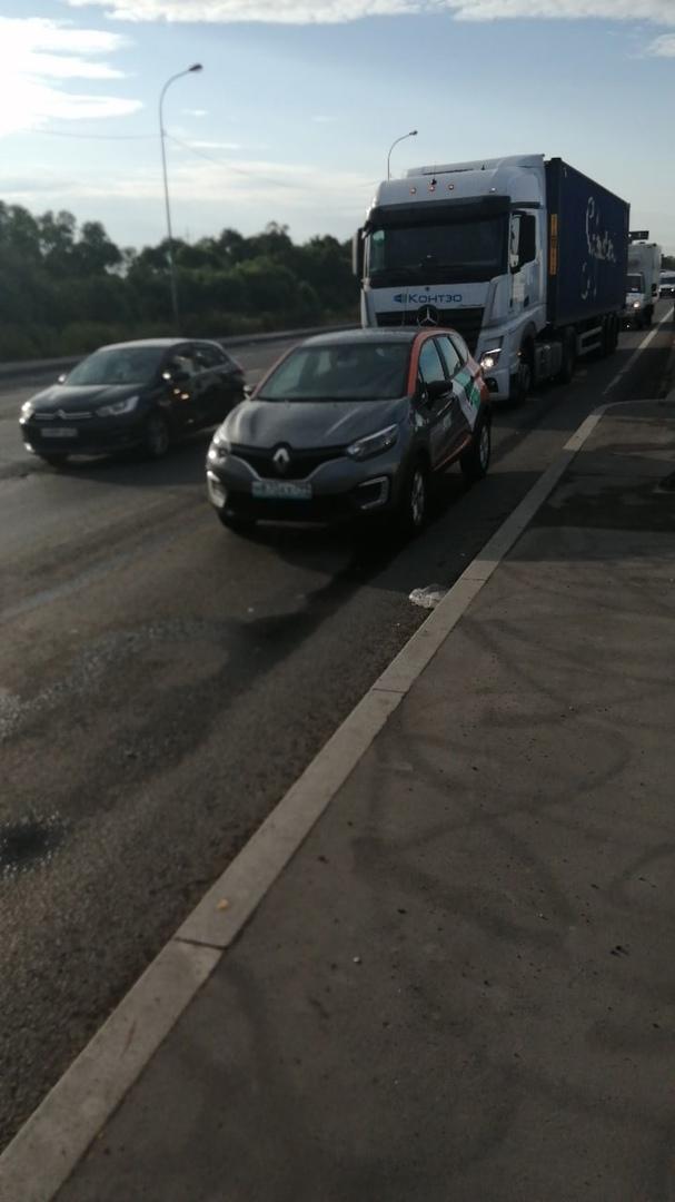 На перекрёстке у Ленты на Московском шоссе в левой полосе стоит автомобиль каршеринга Делимобиль без...