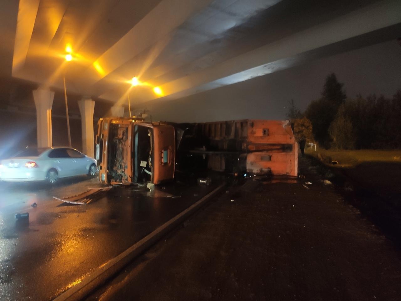 На дороге в Бугры под КАД упал самосвал, зацепив мост открытым бортом.