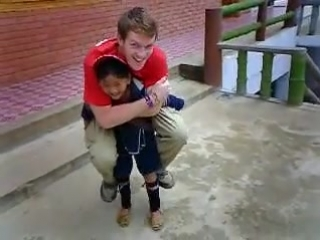 little asian girl lifts adult man easily on her back