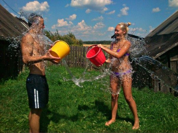 Хлопець і дівчина обливаються водою