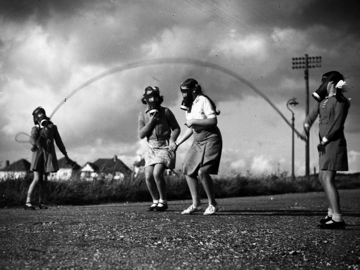 Девочки в противогазах резвятся на переменке, Лондон, Великобритания, 27 июня 1940 года.