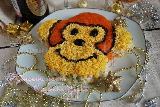 """Оливье готовят к Новому году практически в каждой семье. Именно поэтому мы и решили сделать новогодний салат """"Обезьяна"""" 2016 по рецепту любимого салата, но подать его не в традиционной хрустальной вазе, а на плоской тарелке в форме обезьяньей головы. Салат на Новый год 2016 Обезьяны особенно порадует детишек, наверняка они попросят приготовить его еще раз. 🎅🎄🎁 Из украшений берем самые простые продукты, которые входят и в классический состав закуски, а также нарезанные маслинки.…"""