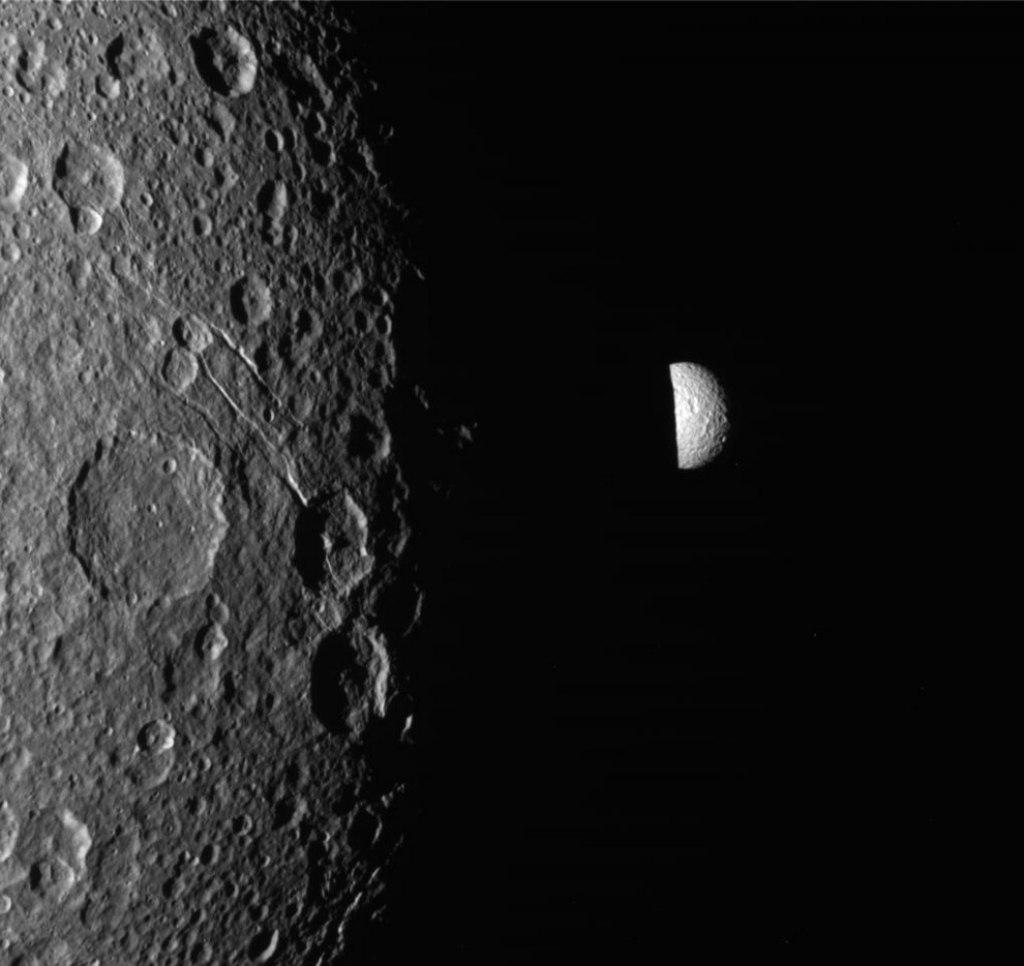 Мимас, один из спутников Сатурна, выглядывает из-за неосвещенной стороны Дионы