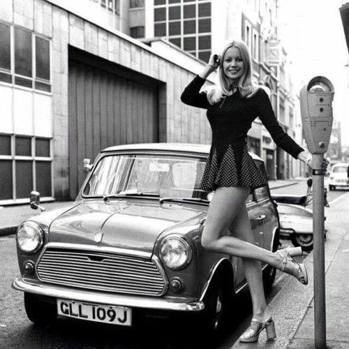 Девушка в мини-юбке позирует возле мини-машины