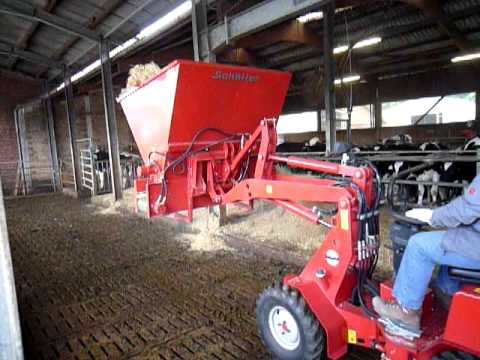 Schaeffer 2027 pivot steer yard loader fitted with a straw dispensing attachment.