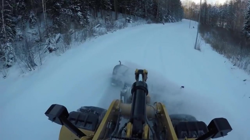 Фронтальный погрузчик с отвалом расчищает снег, вид из кабины