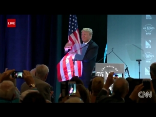 US President Trump hugged an American flag as he walked off the stage at a small business event