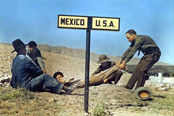 Два американских пограничника пытаются удержать беглеца, который уже успел частично пересечь границу с Мексикой (Эль-Пасо, штат Техас, США, 1939 года