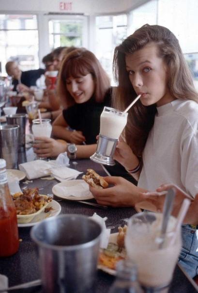 Милла Йовович с гамбургером и молочным коктейлем 1987г.Голливуд