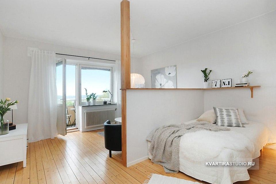 Зонирование совмещенной гостиной-спальни низкой перегородкой.