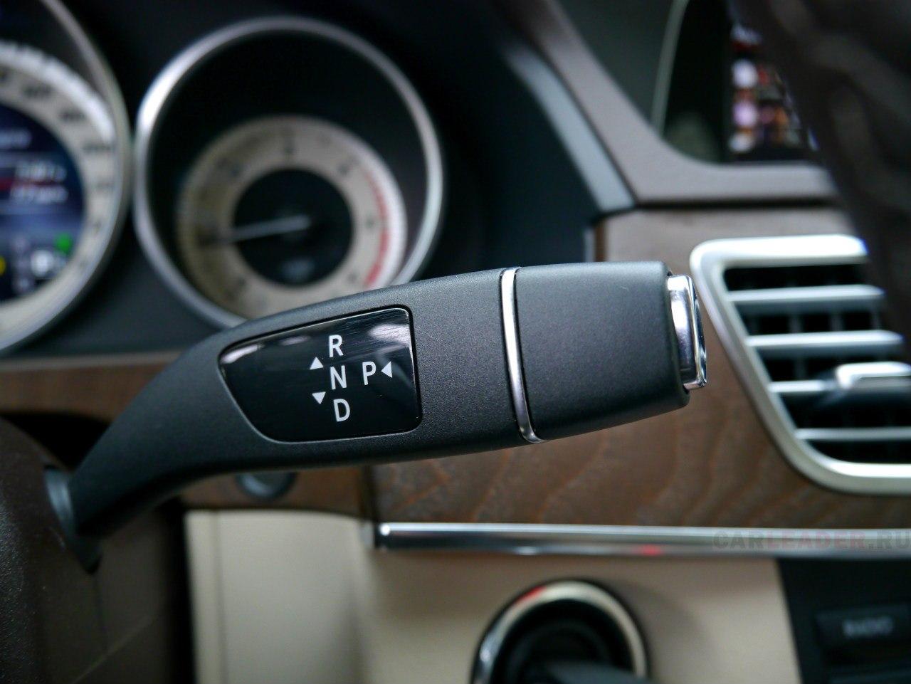 Рукоять автомата Mercedes E 2014 - на рулевой колонке. Решение оригинальное, но спорное. Придется привыкать не путать с дворниками: не нажать на ходу хромированную кнопку и не включить заднюю.