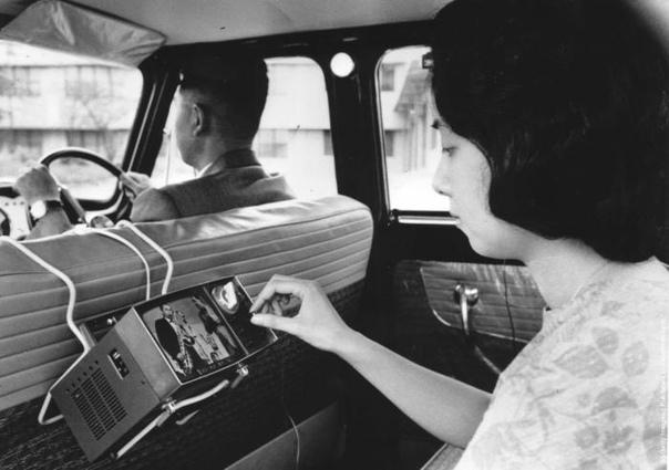 Женщина смотрит портативный телевизор SONY (модель TV5303), сидя на заднем сидении.