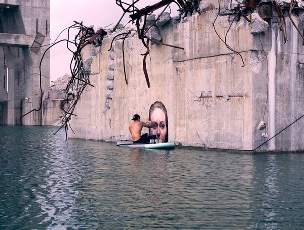 Балансируя на доске для серфинга, художник рисует прекрасное Уличный художник Шон Йоро, известный в социальных сетях как Hula, придумал интересный способ нанесения граффити на стены заброшенных