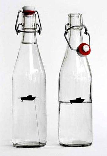 Бутылка с лодочкой внутри.