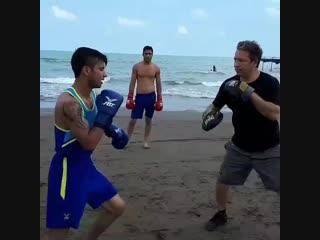Работа на лапах на берегу моря иранских перспективных боксеров-любителей.